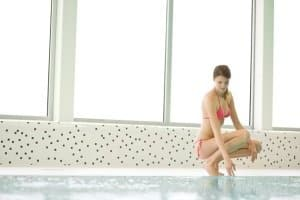 A woman in bikini checking water in a swimming pool